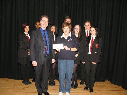 Headmaster Mr presents Miss Allan with the cheque whilst a group of year 11 pupils look on.